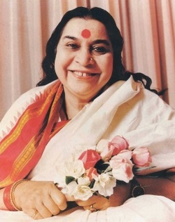 Shri Mataji Nirmala Devi sitting, smiling and holding a bouquet of roses