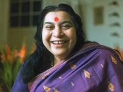 Shri Mataji smiling, head and shoulders in purple sari