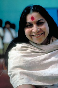 Shri Mataji smiling, in grey shawl